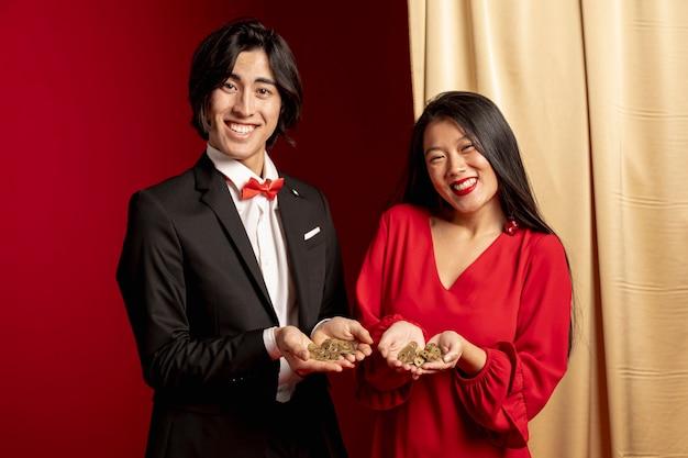 Coppia la posa mentre tengono le monete cinesi dorate per il nuovo anno