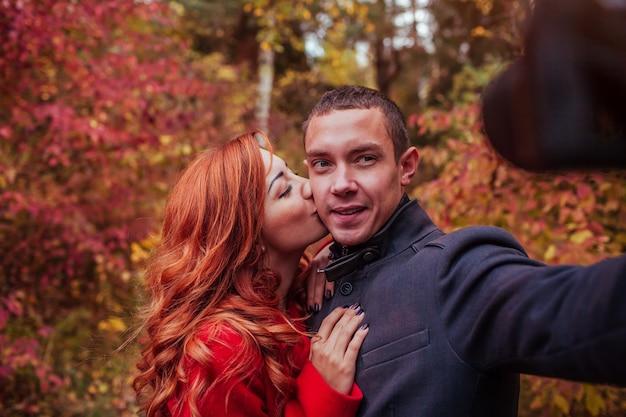 Coppia la presa del selfie facendo uso della macchina fotografica nella foresta di autunno