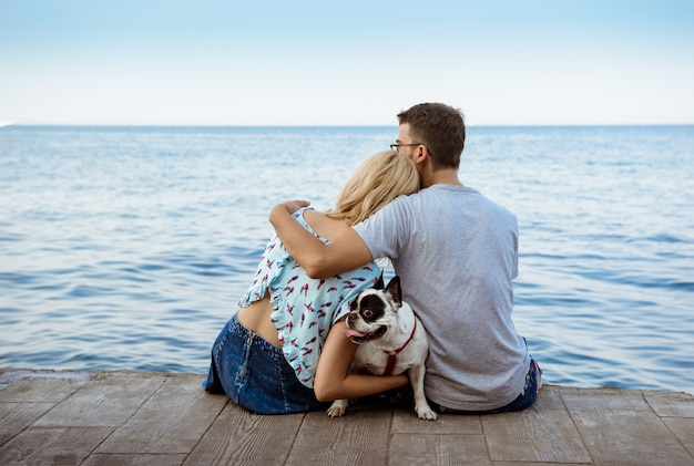 Coppia la seduta con il bulldog francese vicino al mare