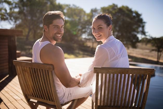 Coppia la seduta insieme sulla sedia alla vacanza di safari