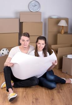 Coppia la seduta sul pavimento domestico che esamina i programmi della casa.