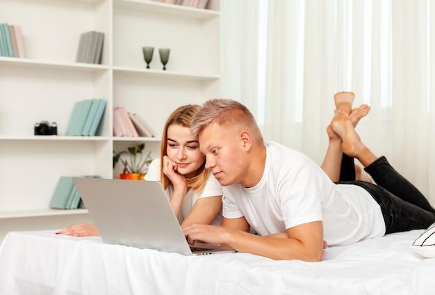 Coppia la visione del film sul loro computer portatile a letto