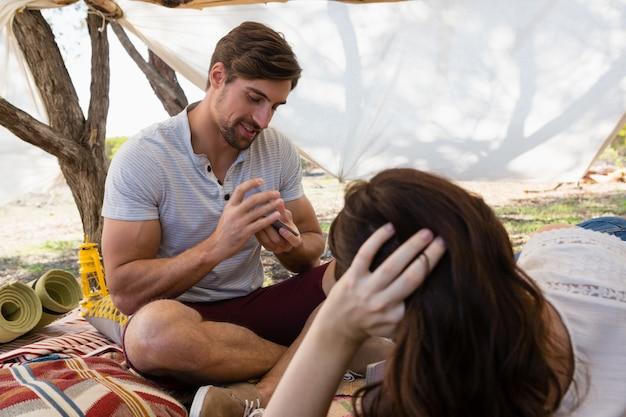 Coppia le carte da gioco mentre riposa in tenda