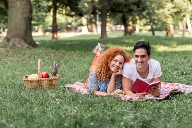 Coppia leggendo un libro insieme al parco