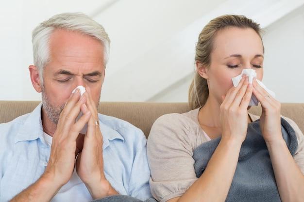 Coppia malata che soffia i loro nasi seduti sul divano