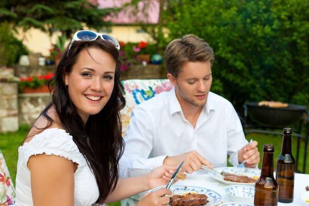 Coppia mangiare il barbecue in giardino con bottiglie di birra sul tavolo