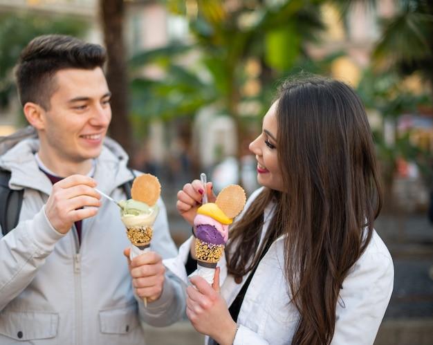 Coppia mangiare un gelato in una strada cittadina