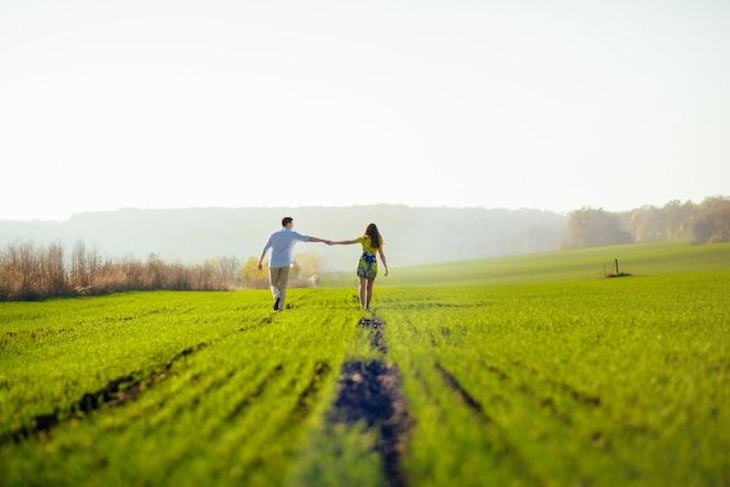 Coppia mano nella mano in una coltura verde
