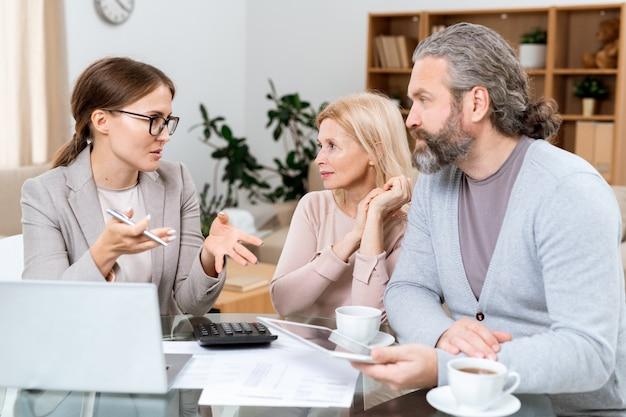 Coppia matura e agente immobiliare seduti a tavola in soggiorno e discutendo di punti finanziari