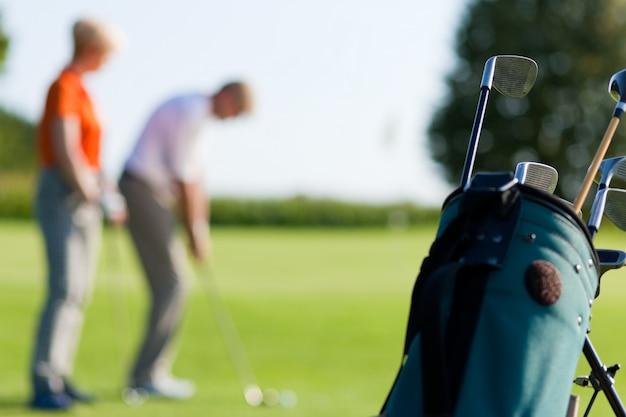 Coppia matura giocando a golf (concentrarsi sulla borsa)