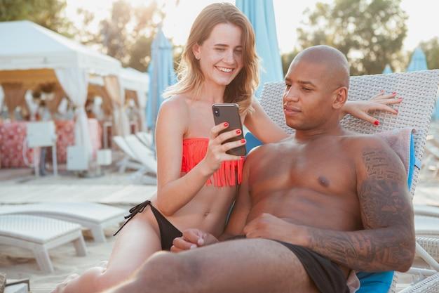 Coppia multirazziale adorabile che prende il sole insieme alla spiaggia, facendo uso dello smart phone. bella donna che mostra qualcosa online per il suo bel ragazzo