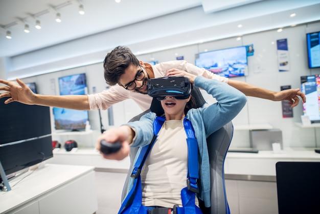 Coppia multirazziale divertendosi con occhiali vr mentre ragazza seduta sulla sedia nel negozio di tecnologia. servizio clienti. tempo di shopping.