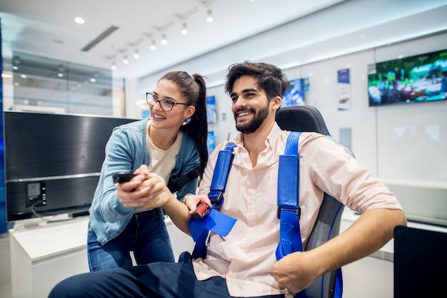 Coppia multirazziale divertendosi con occhiali vr mentre ragazzo seduto sulla sedia nel negozio di tecnologia. servizio clienti. tempo di shopping.
