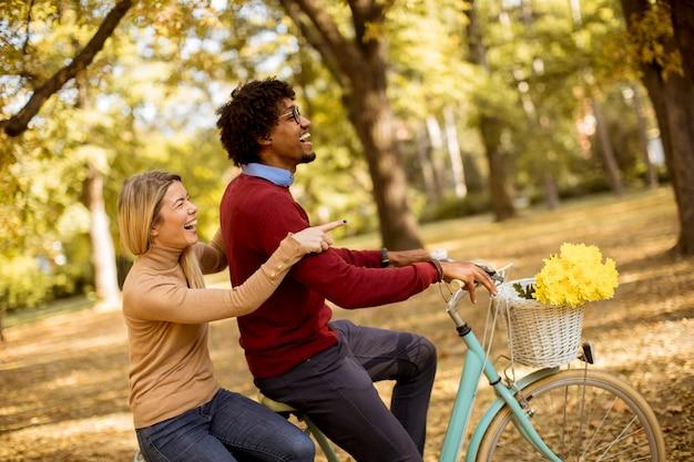 Coppia multirazziale in sella a una bicicletta in autunno parco