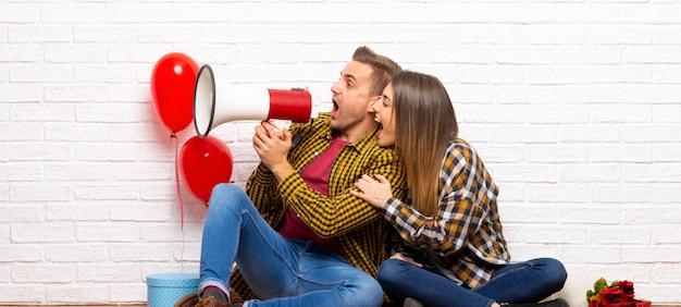 Coppia nel giorno di san valentino al chiuso che grida attraverso un megafono