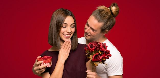 Coppia nel giorno di san valentino con fiori e regali su sfondo rosso