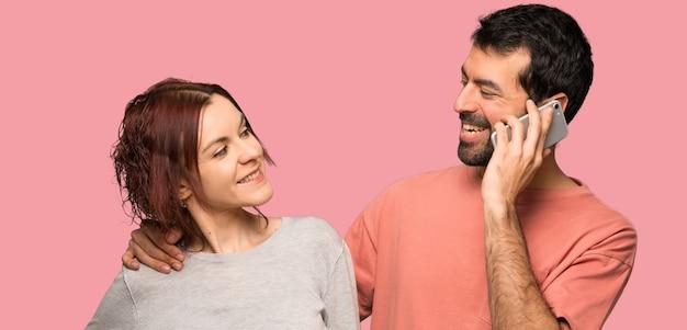 Coppia nel giorno di san valentino mantenendo una conversazione con il telefono cellulare su sfondo rosa isolato