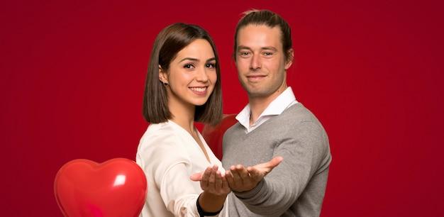 Coppia nel giorno di san valentino tenendo copyspace immaginario sul palmo per inserire un annuncio