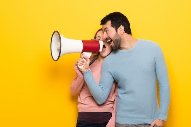 Coppia nel giorno di san valentino urlando attraverso un megafono