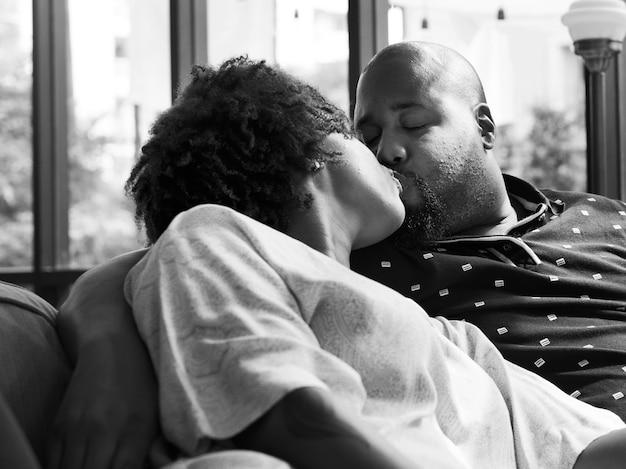 Coppia nera che si bacia sul divano