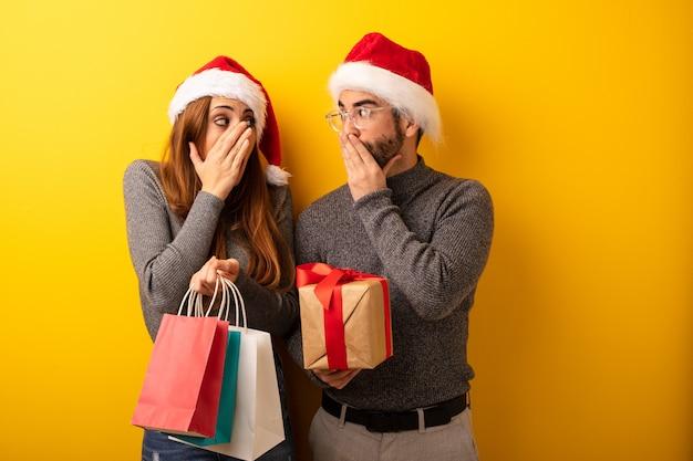 Coppia o amici in possesso di regali e borse della spesa molto spaventati e spaventati nascosti