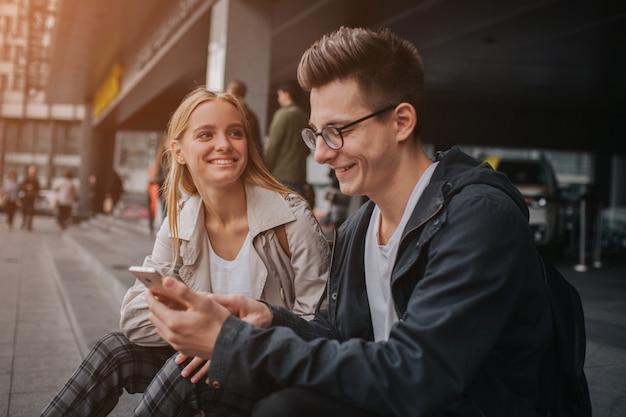 Coppia o amici ridendo divertente e divertirsi con uno smart phone in una grande strada cittadina.