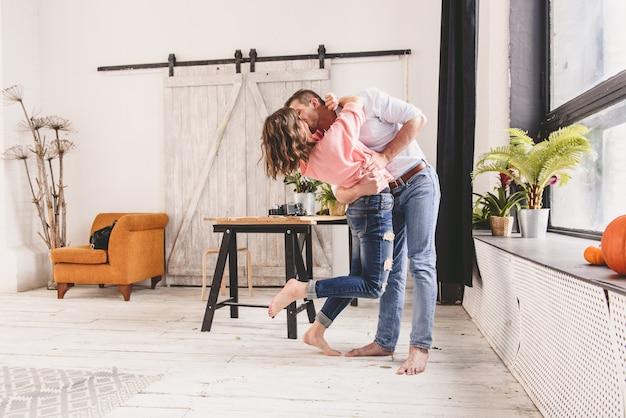 Coppia o matrimonio nella sua nuova casa guardando attraverso la finestra