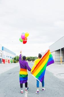 Coppia omosessuale che cammina lungo la strada tenendo palloncini e bandiere lgbt