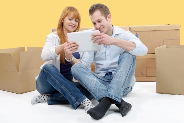 Coppia organizzare nuovo appartamento con tavoletta digitale