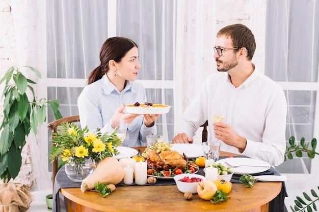 Coppia parlando al tavolo festivo