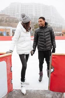 Coppia pattinare insieme e tenendosi per mano alla pista di pattinaggio all'aperto