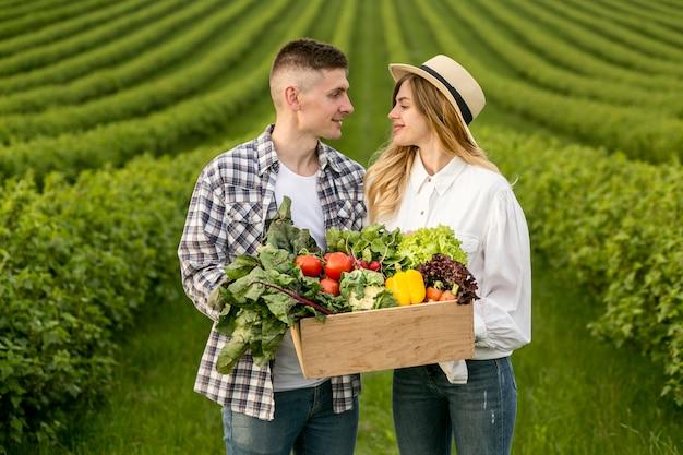 Coppia portando cesto di verdure