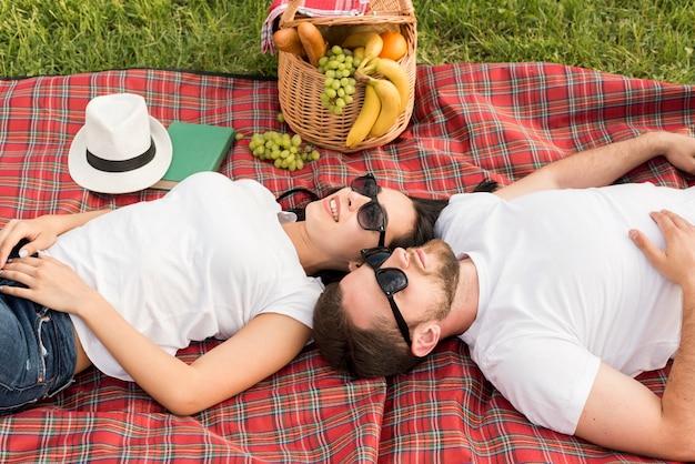 Coppia posa su una coperta da picnic
