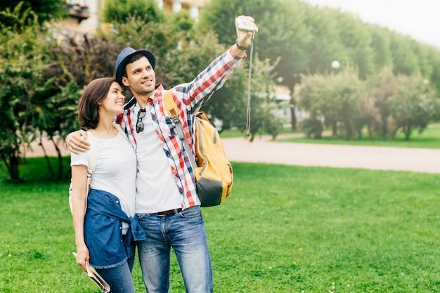 Coppia romantica in amore indossando abiti casual, mentre in piedi sull'erba verde, abbracciati e facendo selfie, sorridendo piacevolmente nella fotocamera. giovane maschio e femmina a visitare la città