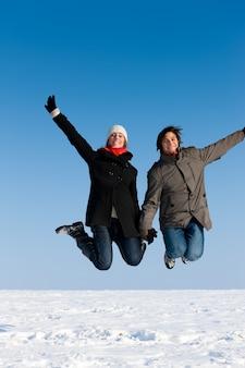 Coppia saltando in una giornata invernale