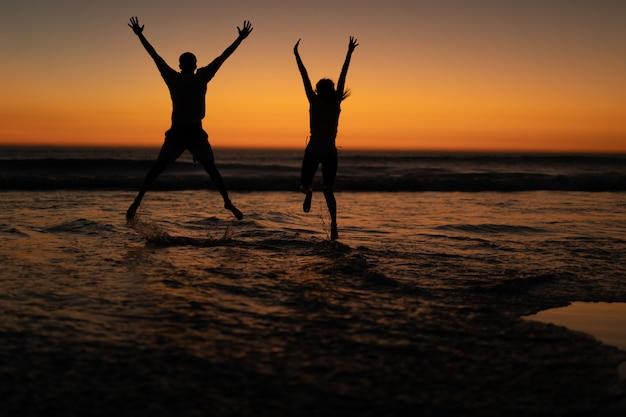 Coppia saltando insieme con le braccia in alto sulla spiaggia