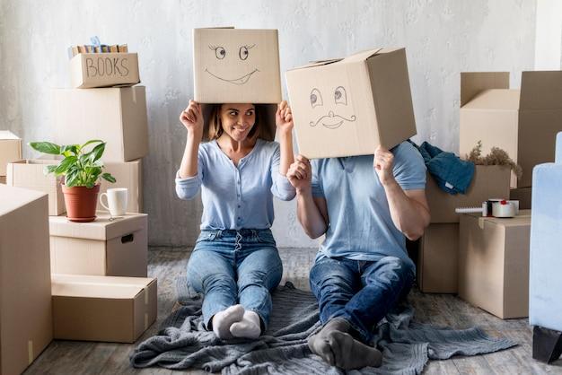 Coppia sciocca con scatole sopra le teste a casa il giorno del trasloco