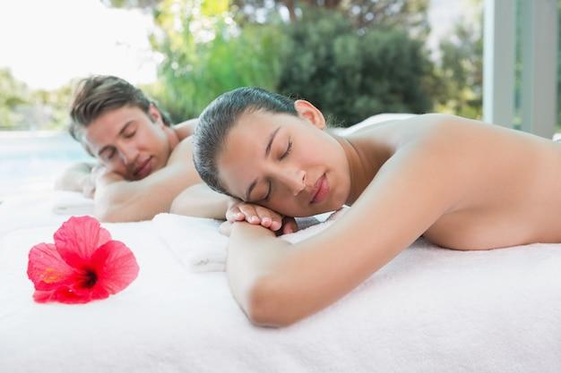 Coppia sdraiata sul lettino da massaggio al centro benessere