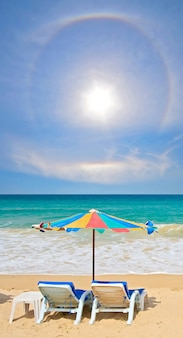 Coppia sedia e ombrello multicolore sulla spiaggia con cielo perfettamente