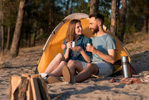 Coppia seduta accanto alla tenda e bevendo