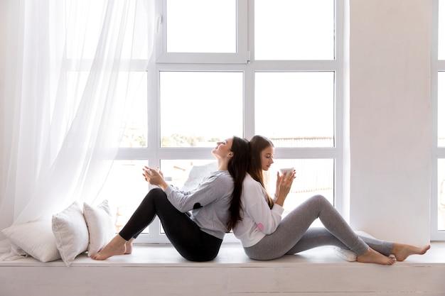 Coppia seduta schiena contro schiena vicino alla finestra