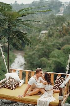 Coppia seduta su una grande altalena su una bali
