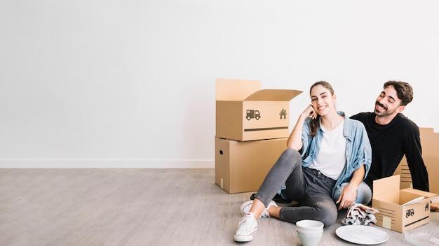 Coppia seduta sul pavimento in nuovo appartamento