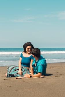 Coppia seduta sulla spiaggia e guardando a vicenda