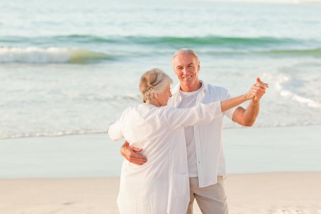 Coppia senior ballando sulla spiaggia