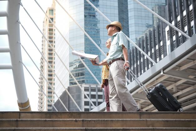 Coppia senior cammina, trascina i bagagli e tiene in mano una mappa per navigare per le strade.