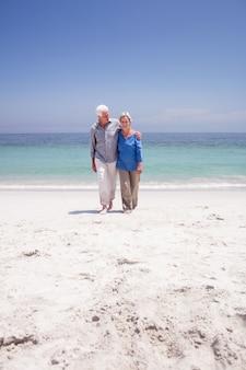 Coppia senior camminando sulla spiaggia