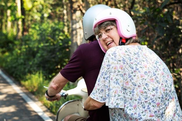 Coppia senior in sella a uno scooter classico