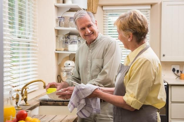 Coppia senior lavare i piatti