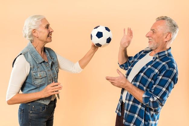 Coppia senior moderna con il calcio